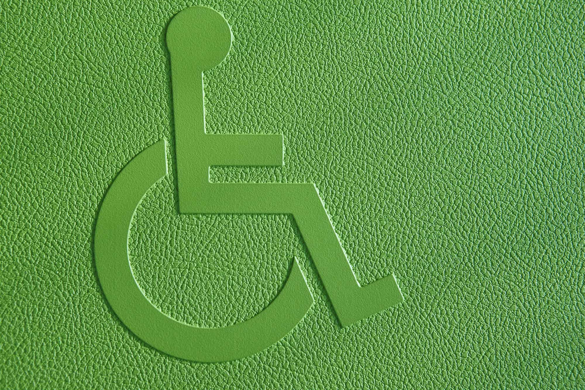 Disabled symbol on a green textured background. Horizontal